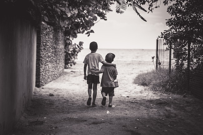 two kids walking away hugging